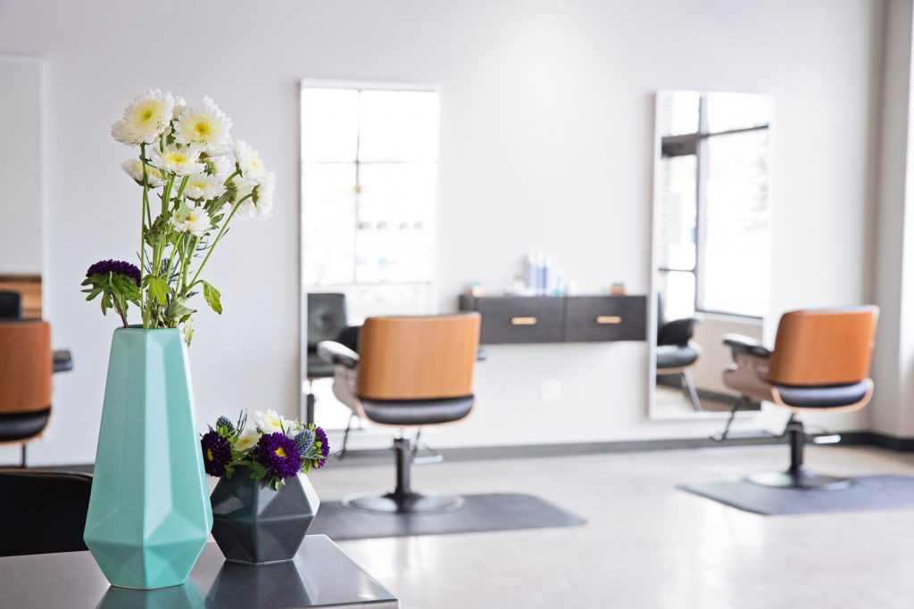 E+L Salon has an industrial modern vibe, with accents of reclaimed wood, stainless steal and sear suckered leather chairs.