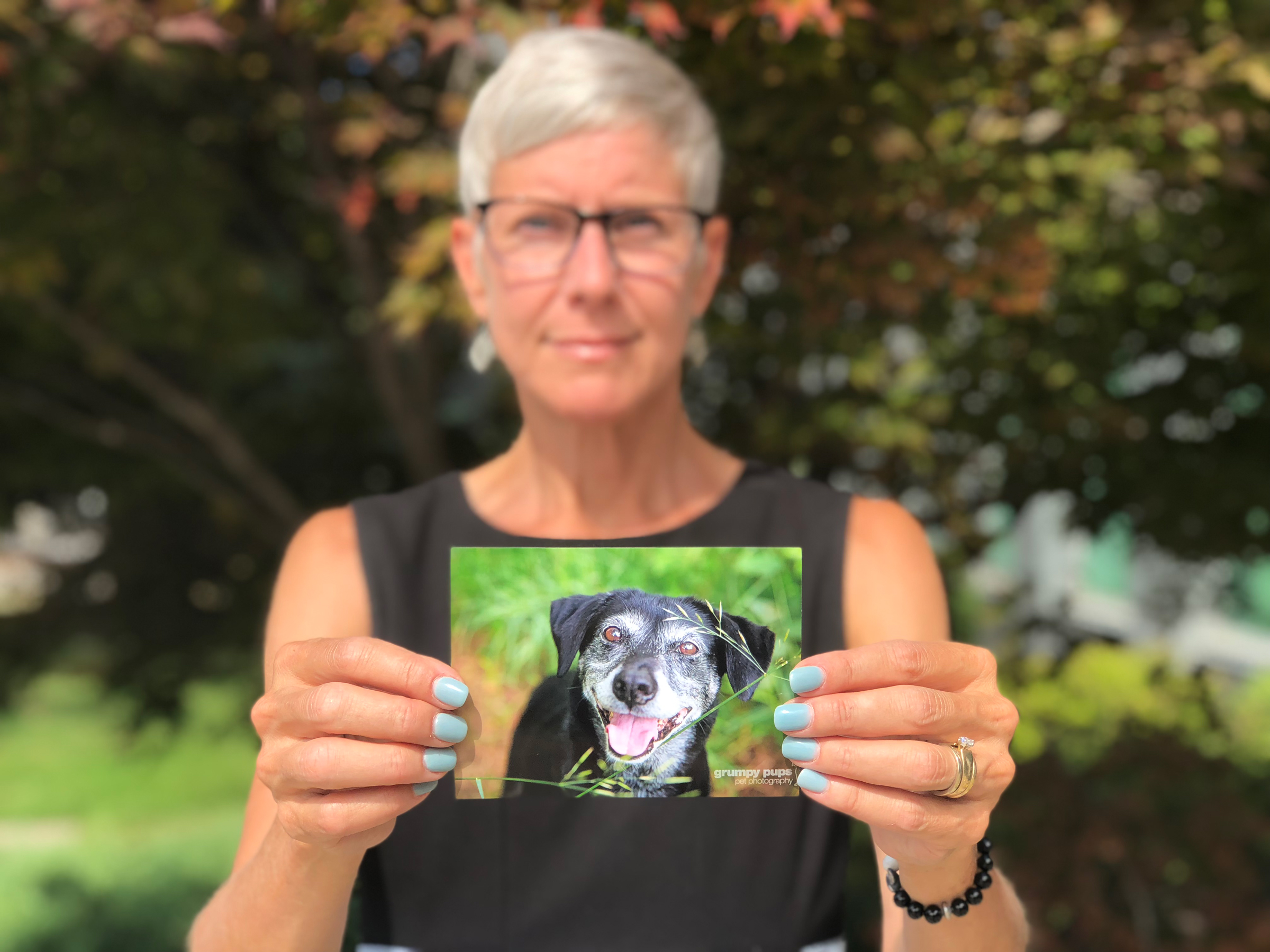 Ginny Mikita holds a photo of her 13-year-old dog Kadie.