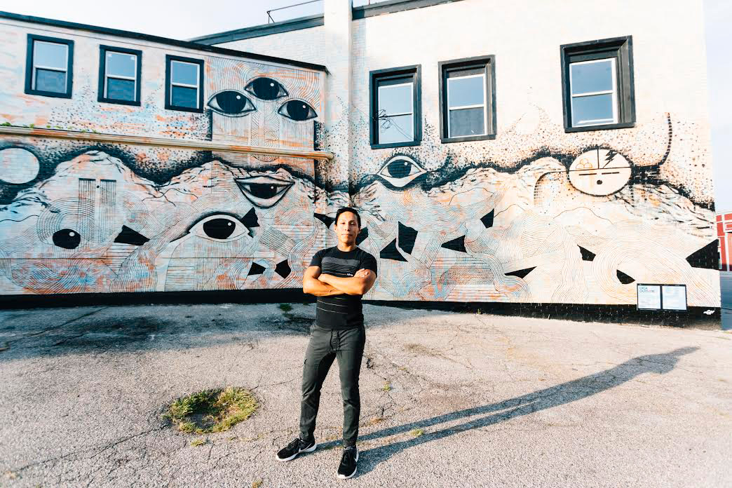 Colby Roanhorse in front of his mural in the Creston neighborhood.