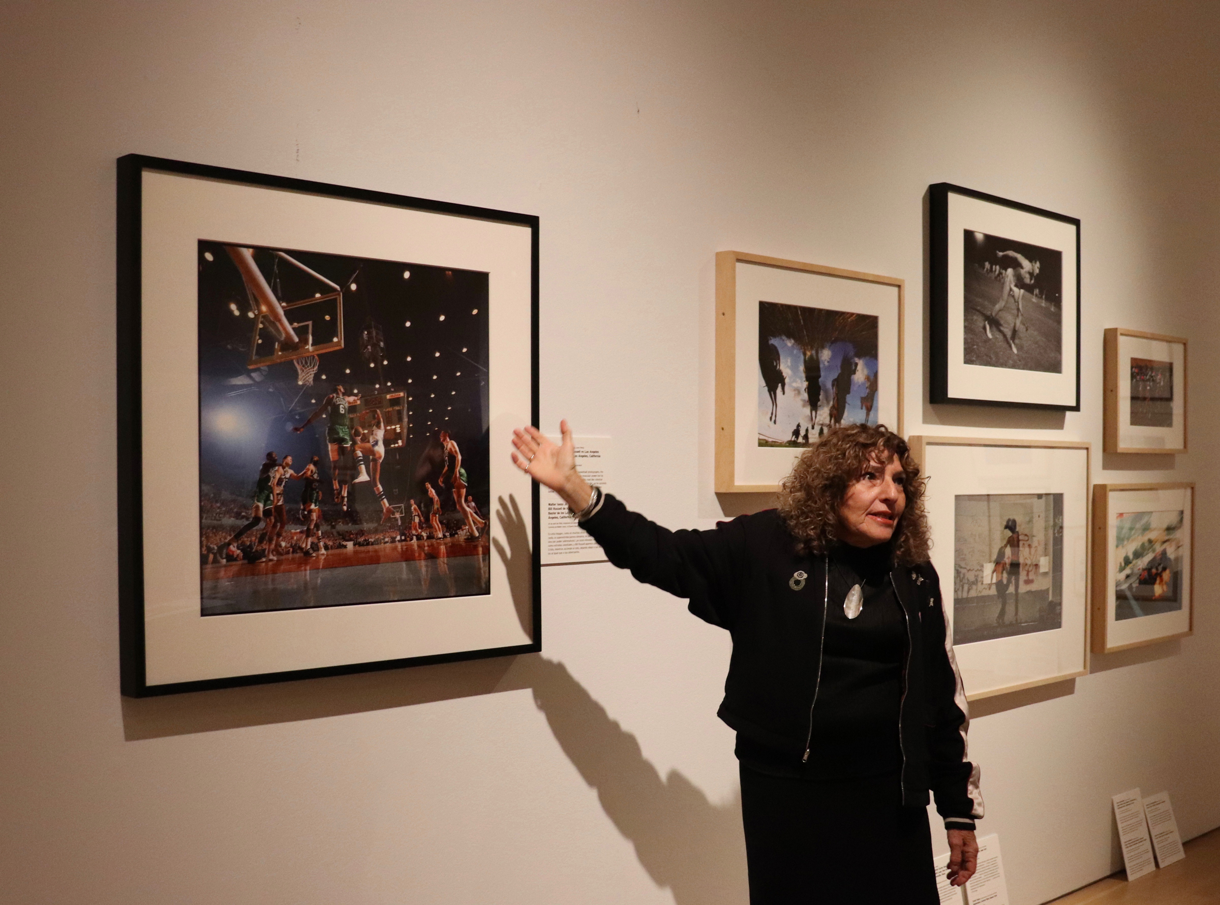 *Main photo: Gail Buckland is the curator of the new exhibition at the Grand Rapids Art Museum featuring sports photography from the 1840s to the present. At her left is a striking image of the 1966 NBA Finals. (Photo by Sam Easter for GR|MAG)